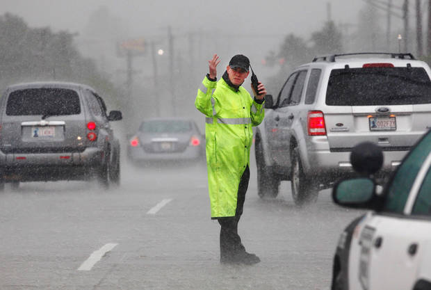A state trooper stands in heavy rain directing traffic near Western and I-44 as traffic exits the interstate where it had come to a near standstill. Torrential rain caused flooding in Oklahoma City, Monday, June 14, 2010.     by Jim Beckel, The Oklahoman
