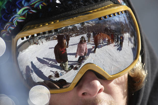 This Nov. 13, 2012 photo shows the reflection of skiers as they gather in line for the chair lift during the first day of their ski season at the Brighton Ski Resort in the Wasatch Range, in Utah. The Brighton Ski Resort is in middle of the Wasatch Range's 7 resorts. If the resorts were to be combined, the Utah resorts could offer North America's largest skiing complex _ three times the size of Vail and twice as big as Whistler Blackcomb in British Columbia. (AP Photo/Rick Bowmer)