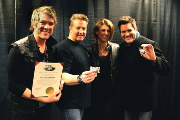 First Lady of Ohio Karen Kasich, second from right, poses for a photo with the members of Rascal Flatts, from left, Joe Don Rooney, Gary LeVox and Jay DeMarcus.