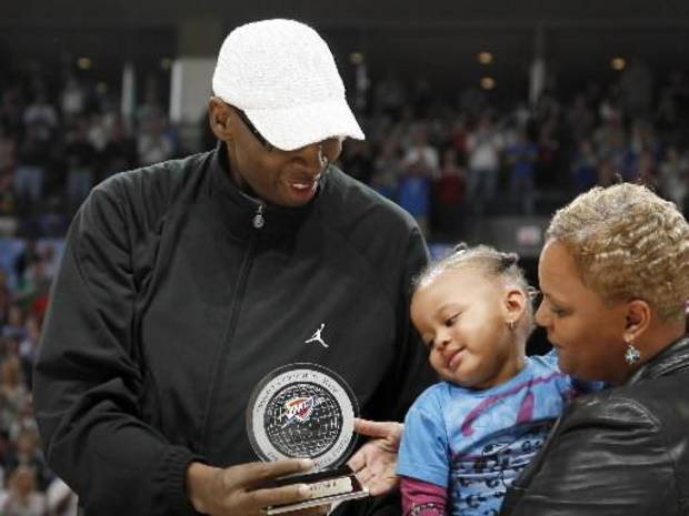 Wayman Tisdale shows his granddaughter, Bailey Braxton, and wife Regina, his Thunder Community Hero award during the NBA game between Oklahoma City and San Antonio, Tuesday April 7, 2009, at the Ford Center in Oklahoma City. Photo by Sarah Phipps