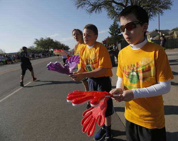 Greyson Gomez, 12, right, Landon Miller, 12, and Gabby Gomez, 15, cheer on runners near NW 63rd and Classen  during the Oklahoma City Memorial Marathon in Oklahoma City, Sunday, April 28, 2013.  Photo by Garett Fisbeck, For The Oklahoman