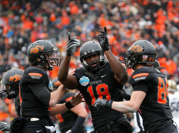 Oklahoma State's Clint Chelf (10), Blake Jackson (18) and Austin Hays (84) celebrate a Jackson touchdown during the Heart of Dallas Bowl football game between Oklahoma State University (OSU) and Purdue University at the Cotton Bowl in Dallas,  Tuesday,Jan. 1, 2013. Photo by Sarah Phipps, The Oklahoman
