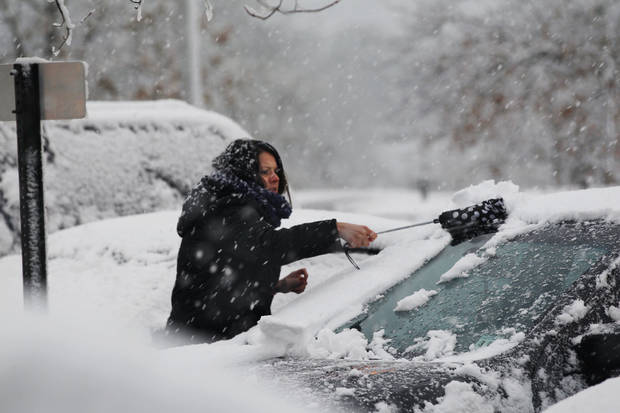 A woman clears snow from her parked car Wednesday, Nov. 7, 2012, in Dover Township, N.J., as the region pounded by Superstorm Sandy last week is hit by a Nor'Easter.  Gov. Chris Christie warned Wednesday that New Jersey may suffer a setback in its Superstorm Sandy recovery efforts as a result of the new storm. (AP Photo/Mel Evans) ORG XMIT: NJME112