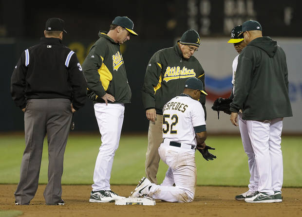 Oakland Athletics' Yoenis Cespedes (52) is attended to by trainers as manager Bob Melvin, second from left, looks on in the eighth inning of a baseball game against the Detroit Tigers Friday, April 12, 2013, in Oakland, Calif. (AP Photo/Ben Margot)
