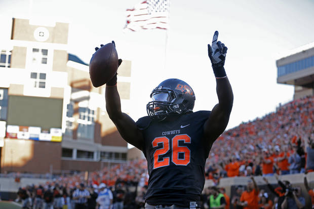 Oklahoma State's Desmond Roland (26) celebrates his touchdown during a college football game between the Oklahoma State University Cowboys (OSU) and the University of Kansas Jayhawks (KU) at Boone Pickens Stadium in Stillwater, Okla., Saturday, Nov. 9, 2013. Photo by Sarah Phipps, The Oklahoman