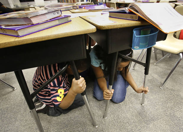 "Fourth-grade students take cover under their desks at Cleveland Bailey Elementary School in Midwest City. They were participated Wednesday in the ""Drop, Cover and Hold-on"" multistate earthquake drill. Photo by Jim Beckel, The Oklahoman <strong>Jim Beckel</strong>"