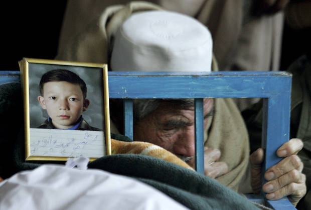 An elderly Pakistani man, reacts next to the body of his grandson Mohammed Javaid, a victim of Saturday's bombing, in a Mosque in Quetta, Pakistan, Sunday, Feb. 17, 2013. Angry residents on Sunday demanded government protection from an onslaught of attacks against Shiite Muslims, a day after scores of people were killed in a massive bombing that a local official said was a sign that security agencies were too scared to do their jobs. (AP Photo/Arshad Butt)