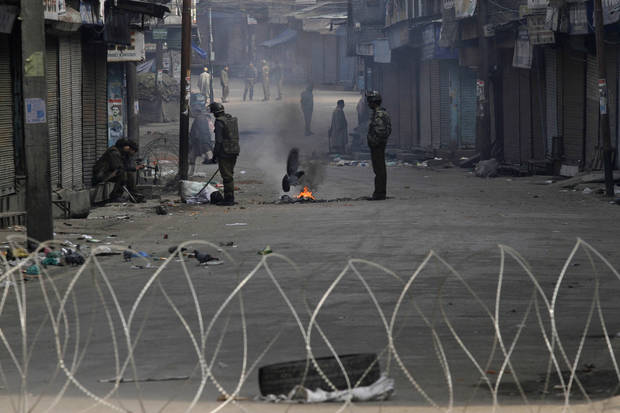 Indian policemen guard a residential area on the fourth consecutive day of curfew imposed after the execution of a Kashmiri man convicted in a deadly 2001 attack on India's Parliament in Srinagar, India, Tuesday, Feb. 12, 2013. Mohammed Afzal Guru was hanged in New Delhi early Saturday. Ahead of the execution, authorities had anticipated anti-India protests and ordered people in most of the Indian-held part of the disputed Kashmir region to remain indoors indefinitely. (AP Photo/Mukhtar khan)
