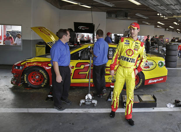 Joey Logano, right, walks away from his car in the garage as his crew looks over damage after he was involved in a crash during NASCAR auto race testing at Daytona International Speedway, Friday, Jan. 11, 2013, in Daytona Beach, Fla. (AP Photo/John Raoux)