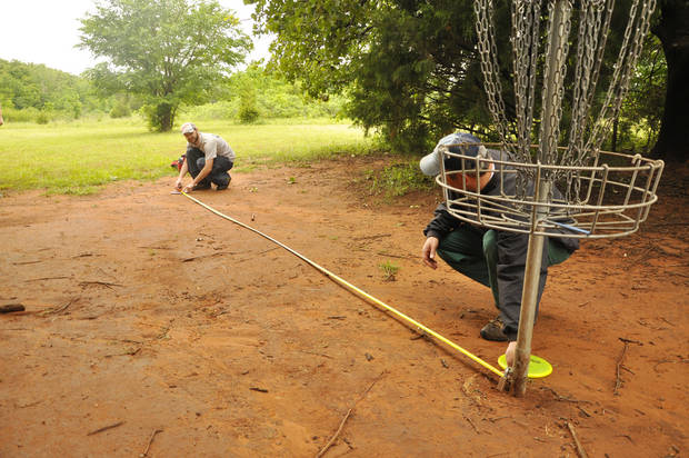 Todd Hopeman and Alex Davis measure for a putt at the disc golf tournament in Edmond.