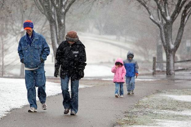 From left, David Kenyon and Kelli Kenyon with their children Katie Kenyon, 5, and Kieran Kenyon, 6, all of Edmond, Okla., take a walk as snow falls at Hafer Park in Edmond, Okla., Saturday, March 28, 2009. PHOTO BY NATE BILLINGS, THE OKLAHOMAN