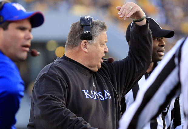Kansas coach Charlie Weis, center, argues with an official during the second quarter of their NCAA college football game against West Virginia in Morgantown, W.Va., on Saturday, Dec. 1, 2012. West Virginia won 59-10.  (AP Photo/Christopher Jackson)