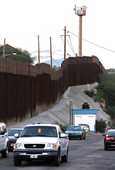 In this photo taken Thursday, Aug. 9, 2012, vehicles drive along the border fence in Nogales, Mexico. A U.S. Border Patrol agent opened fire on a group of people throwing rocks from across the Mexican border, killing a teenage boy and eliciting outrage from the Mexican government over the use of lethal force, authorities said Thursday, Oct. 11, 2012. (AP Photo/Ross D. Franklin)