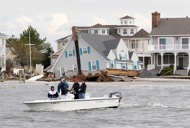 People in a boat pass severely damaged homes Friday, Nov. 2, 2012, along the bayside of Mantoloking, N.J. New Jersey Gov. Chris Christie toured some of the region devastated by Monday's storm surge by superstore Sandy. (AP Photo/Mel Evans, Pool) ORG XMIT: NJME113