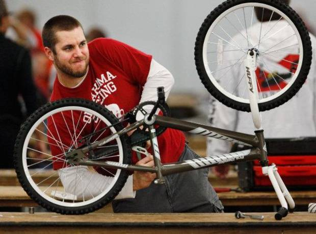 Chad Morris, a member of the Oklahoma Bicycle Society, tightens a bolt on a guard that  covers a bicycle�s chain.