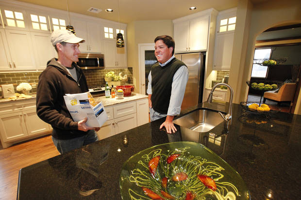Builder Caleb McCaleb, right, and closer Aaron Peterson  talk in  McCaleb�s model home at 732 Road Not Taken  in Edmond. Photo by David McDaniel, The Oklahoman
