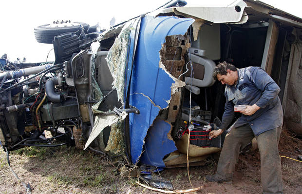 Armando Castillo finds personal items out of his truck that he was driving when it was swept off I-40 and destroyed by a tornado west of El Reno, Tuesday, May 24, 2011. Photo by Chris Landsberger, The Oklahoman ORG XMIT: KOD