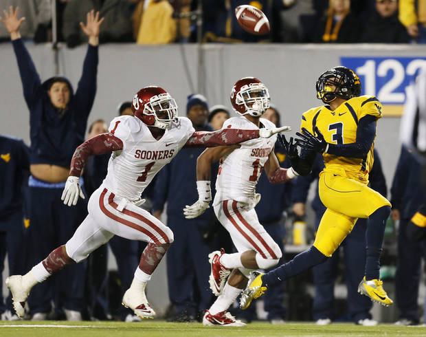 West Virginia's Stedman Bailey (3) catches a touchdown pass against Oklahoma's Tony Jefferson (1) and Oklahoma's Aaron Colvin (14) in the final minutes of the fourth quarter to give the Mountaineers their last lead during a college football game between the University of Oklahoma and West Virginia University on Mountaineer Field at Milan Puskar Stadium in Morgantown, W. Va., Nov. 17, 2012. OU won, 50-49. Photo by Nate Billings, The Oklahoman