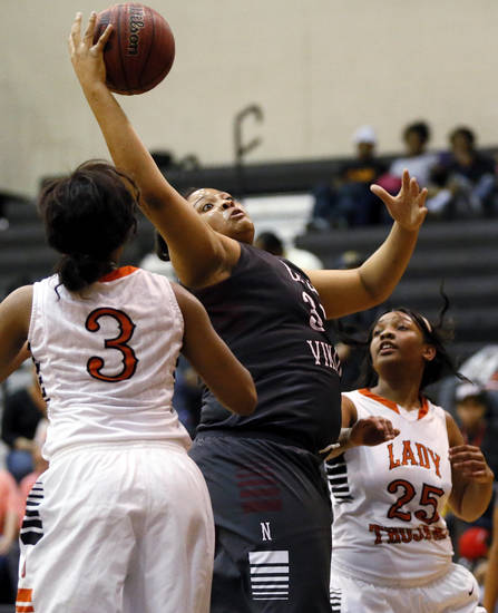 Northeast's Chanel Akins (33) grabs a rebound between Nia Stepeny (3) and LaJuana Morgan (25) during a girls high school basketball game between Douglass and Northeast at Douglass High School in Oklahoma City, Friday, Feb. 8, 2013. Photo by Nate Billings, The Oklahoman