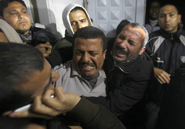 Relatives of a man killed in an Israeli airstrike mourn at a morgue in Gaza City, Friday, March 9, 2012. The Israeli military said in a statement that it targeted two rocket launching positions in the Gaza Strip Friday. (AP Photo/Hatem Moussa) ORG XMIT: DV113