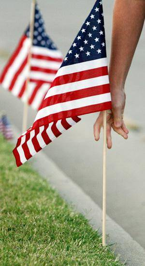 A supporter places an American flag in the ground at the flag line outside the Oklahoma Air National Guard base at Will Rogers World Airport honoring the return home of Chief Warrant Officer Brady Rudolf's body, in Oklahoma City, Friday, September 26, 2008. Rudolf was killed last week in Iraq. BY NATE BILLINGS, THE OKLAHOMAN