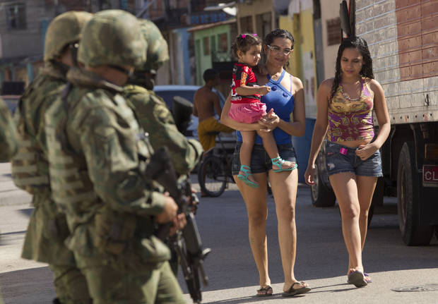 In this Oct. 1, 2012 photo, residents walk through the street as soldiers patrol ahead of municipal elections in the Fogo Cruzado slum of Rio de Janeiro, Brazil. Brazil will hold nationwide municipal elections on Sunday, Oct. 7. (AP Photo/Silvia Izquierdo)