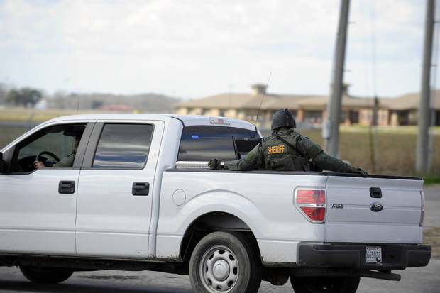 A sheriff's deputy rides in a police vehicles as he leaves the scene of a shooting, Saturday, Jan. 26, 2013 in Charenton, La.  Police on Saturday arrested a man suspected of fatally shooting a police officer and critically wounding two sheriff's deputies after setting a deadly fire at a mobile home near a south Louisiana casino. (AP Photo/The Daily Iberian, Lee Ball)