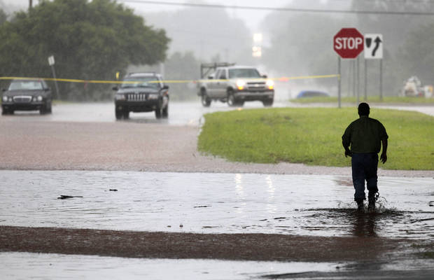 A motorists walks in high water near Britton road and I-35 in Oklahoma City, Oklahoma June 14 , 2010. Photo by Steve Gooch, The Oklahoman