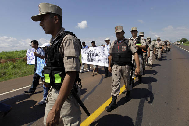 In this Nov. 15, 2012 photo, police escort landless farmers who are demanding the release of fellow farmers who were detained during clashes with police in the Yvy Pyta settlement near Curuguaty, Paraguay.  The &Atilde;&not;Massacre of Curuguaty&Atilde;&reg; on June 15 killed 11 farmers and 6 police officers when negotiations between farmers occupying a rich politician&#039;s land ended with a barrage of bullets. The underlying dispute that set up the clash was decades in the making. The area&#039;s poor residents have long alleged that the land was effectively stolen from the state by Sen. Blas Riquelme, a leader of the Colorado Party that backed dictator Alfredo Stroessner from 1954 to 1989, and has dominated the nation&#039;s politics ever since. (AP Photo/Jorge Saenz)