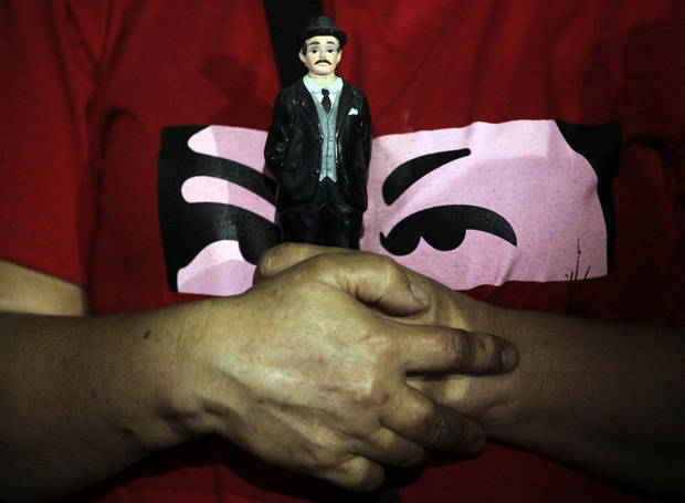 A person holds an image of the Venezuelan saint Jose Gregorio Hernadez  as people gather to pray for Venezuela's President Hugo Chavez at the Simon Bolivar square in Caracas, Venezuela, Tuesday, Dec. 11, 2012. Doctors began operating on Chavez  in Cuba, his government said, after his cancer reappeared despite a year and a half of surgeries and treatments. (AP Photo/Fernando Llano)