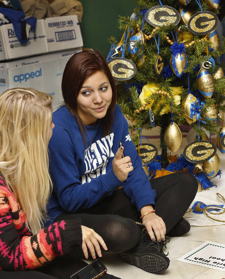 Sarah Howells, right, a Guthrie High School senior, talks to Kayla Means, a junior,  after they and other art students finished decorating their tree, shown in background, on the first floor rotunda at the capitol. The theme of the school's tree is 'Home of Champions' and it celebrates the various state championships the school has won. School children from across the state came to the state Capitol  to decorate 36  small Christmas trees in the hallways and rotunda.  Gov. Mary Fallin and State Superintendent Janet Barresi joined Santa Claus in greeting the students at each tree after they were decorated. Many of the children stayed to watch the  governor light the state Christmas tree on the south plaza on Thursday,  Nov. 29, 2012.   Photo by Jim Beckel, The Oklahoman