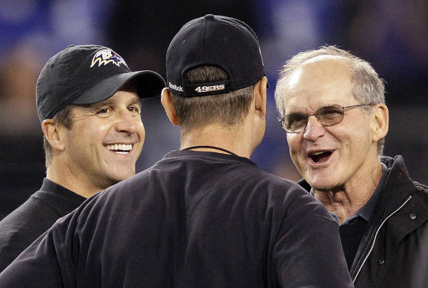 FILE - In this Nov. 24, 2011 file photo, Baltimore Ravens head coach John Harbaugh, left, and his brother, San Francisco 49ers head coach Jim Harbaugh, talk with their father, Jack, right, before their NFL football game in Baltimore. The Harbaughs, San Francisco's Jim and Baltimore's John, will be the first pair of brothers to coach against each other in the NFL title game. (AP Photo/Patrick Semansky, File)