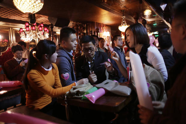"Participants who are singles introduce themselves during a matchmaking party organized by one of the biggest Chinese matchmaking websites in Shanghai, China on Sunday Nov. 11, 2012. Singles Day was begun by Chinese college students in the 1990s as a version of Valentine's Day for people without romantic partners. The timing was based on the date Nov. 11, or ""11.11"" � four singles. Unattached young people would treat each other to dinner or give gifts to woo that special someone and end their single status. (AP Photo/Eugene Hoshiko)"