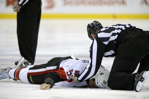 Ottawa Senators left wing Dave Dziurzynski (59) is helped by a linesman after a fight against Toronto Maple Leafs' Frazer McLaren during first-period NHL hockey game action in Toronto, Wednesday, March 6, 2013. (AP Photo/The Canadian Press, Frank Gunn)