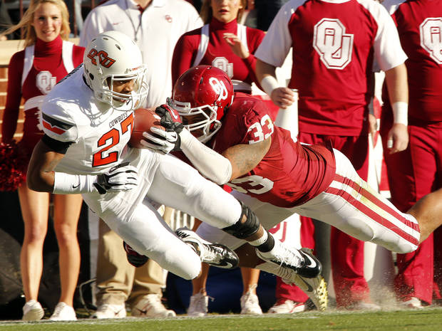 Oklahoma State's Lyndell Johnson (27) is brought down after an interception by Oklahoma's Trey Millard (33) during the Bedlam college football game between the University of Oklahoma Sooners (OU) and the Oklahoma State University Cowboys (OSU) at Gaylord Family-Oklahoma Memorial Stadium in Norman, Okla., Saturday, Nov. 24, 2012. Photo by Steve Sisney, The Oklahoman