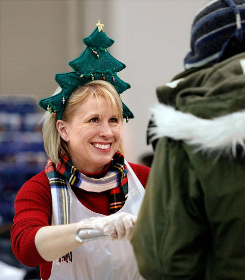 "Wearing a festive headpiece, volunteer Debbie Yoeckel, Edmond, serves up food with a smile to persons attending the Red Andrews Dinner at the Cox Convention Center, Friday,  Dec. 25, 2009.  This is her seventh year to volunteer at the charity event. Yoeckel said she and her husband arrived at 7 a.m. to make 24 trays of mashed potatoes with a mixer that is ""taller than I am."" Photo by Jim Beckel, The Oklahoman"