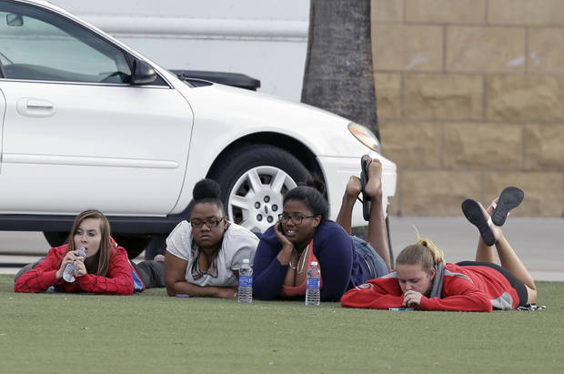 University of Central Florida students wait outside the college sports arena after explosive devices were found in a nearby dorm, Monday, March 18, 2013, in Orlando, Fla. The campus was closed and classes were postponed until noon. (AP Photo/John Raoux)