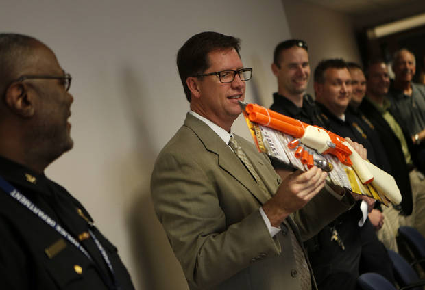 Norman police Capt. Darry Stacy is presented with a going-away gift at a retirement reception Friday. PHOTOS BY GARETT FISBECK, THE OKLAHOMAN