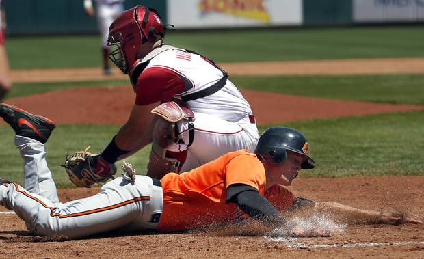 Oklahoma State's  Gage Green slides safe into home as Oklahoma's Anthony Hermelyn prepares to make a tag during the Bedlam baseball game between the University of Oklahoma and Oklahoma State University at the Chickasaw Bricktown Ballpark in Oklahoma CIty, Sunday, May 12, 2013. Photo by Sarah Phipps, The Oklahoman