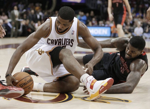 Cleveland Cavaliers' Tristan Thompson, left, and Toronto Raptors' Amir Johnson scramble for a loose ball during the fourth quarter of an NBA basketball game Wednesday, Feb. 27, 2013, in Cleveland. The Cavaliers won 103-92. (AP Photo/Tony Dejak)