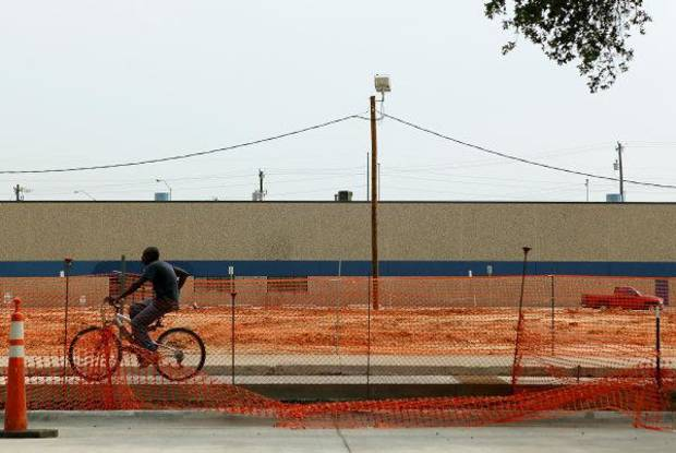A man rides his bike past the recommended site for the proposed convention center west of the Oklahoma City Arena on Reno in Oklahoma City. Photo by John Clanton, The Oklahoman <strong>John Clanton</strong>