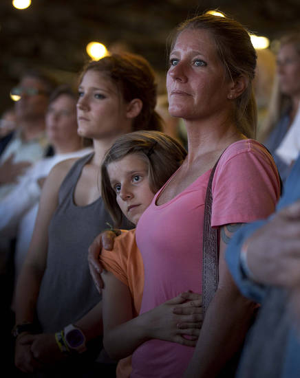 A woman stands with her family as a prayer is said over the loudspeakers at the Prescott Frontier Days Rodeo, Wednesday, July 3, 2013 in Prescott, Ariz., for the 19 Granite Mountain Hotshot firefighters who were killed Sunday near Yarnell, Ariz. (AP Photo/Julie Jacobson)