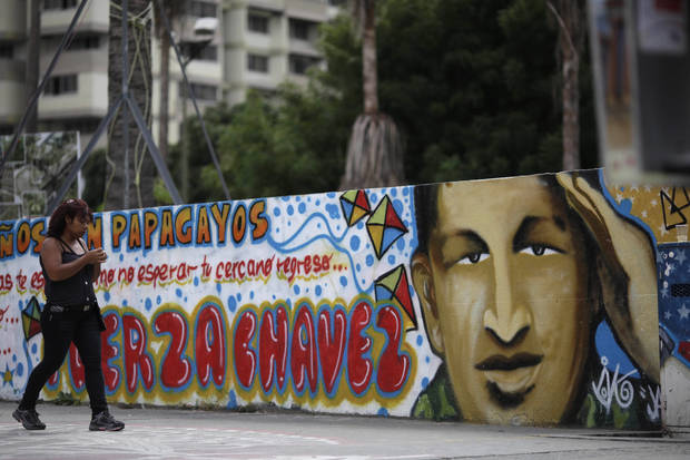 "A woman walks past a mural of Venezuela's President Hugo Chavez in Caracas, Venezuela, Monday, Dec. 31, 2012.  Chavez is confronting ""new complications"" due to a respiratory infection nearly three weeks after undergoing cancer surgery, his Vice President Nicolas Maduro said Sunday evening in Cuba as he visited the ailing leader for the first time since his operation. (AP Photo/Ariana Cubillos)"