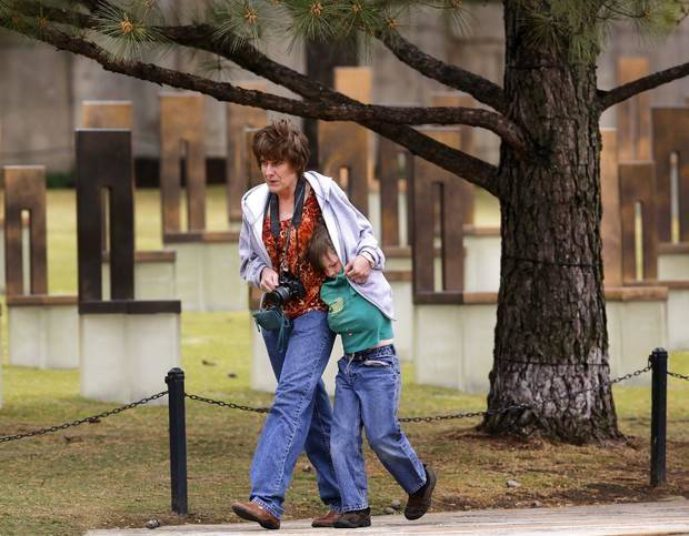 Wendy Lindsey huddles with her son, Weston, 7, covering him with her jacket while visiting the memorial Thursday morning. Wendy brought Weston and another son, Morgan, to the memorial during a visit to Oklahoma City from their home in Lincoln, AR. Predicted cold temperatures and other weather factors prompted officials to move Friday's ceremony commemorating the 18th anniversary of the bombing of the Murrah Federal Building to an indoor venue near the Oklahoma City National Memorial in downtown Oklahoma City. Photo by Jim Beckel