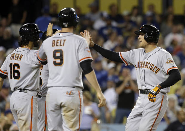 San Francisco Giants' Hunter Pence, right, is greeted at the plate by Angel Pagan, Brandon Belt and Tim Lincecum, hidden at rear, as all score on Pence's grand slam against the Los Angeles Dodgers in the fifth inning of a baseball game in Los Angeles on Saturday, Sept. 14, 2013. (AP Photo/Reed Saxon)