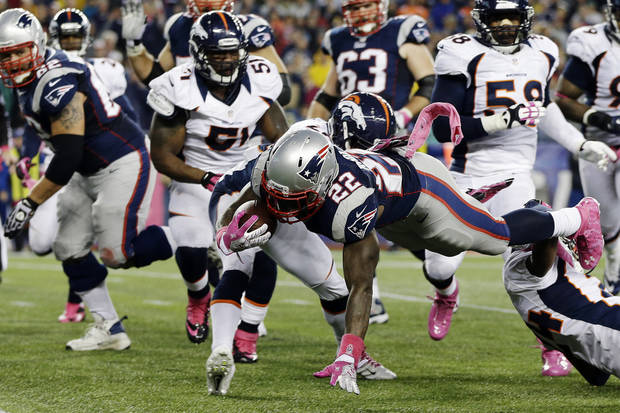 New England Patriots running back Stevan Ridley (22) is tripped up while rushing against Denver Broncos safety Rahim Moore (26) and cornerback Champ Bailey (24) on his way to a touchdown in the third quarter of an NFL football game, Sunday, Oct. 7, 2012, in Foxborough, Mass. (AP Photo/Elise Amendola)