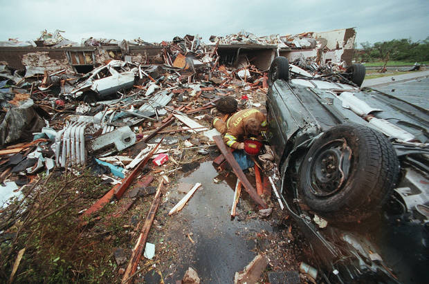 MAY 3, 1999 TORNADO: Tornado damage: Midwest City firefighter Dave Roberts checks for victims at the Hampton Inn in Midwest City.