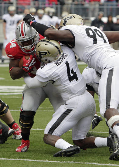 Ohio State running back Carlos Hyde, left, runs the ball against Purdue defenders Taylor Richards, center, and Ryan Russell during the fourth quarter of an NCAA college football game Saturday, Oct. 20, 2012, in Columbus, Ohio. Ohio State beat Purdue 29-22 in overtime. (AP Photo/Jay LaPrete)
