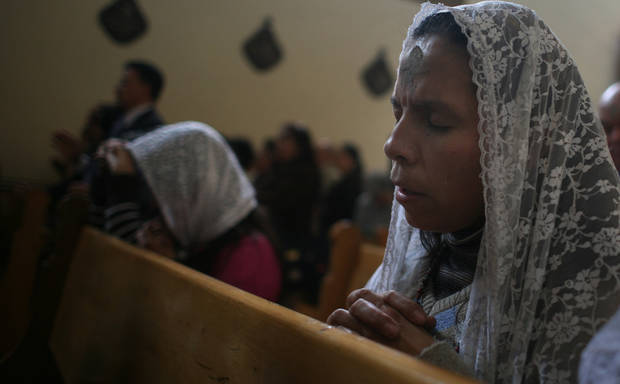 A woman prays during an Ash Wednesday mass at a Catholic church in Bogota, Wednesday, Feb. 25, 2009. Traditionally priests place ashes on the foreheads of the catholic faithful on Ash Wednesday, that marks the start of the Lent, the season of prayer and fasting before Easter. (AP Photo/William Fernando Martinez)