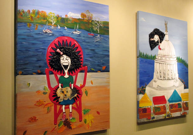 Paintings imagining comedian Gilda Radner in recognizable locations in Madison hang on the wall inside the cancer support group Gilda's Club Madison on Wednesday, Nov. 27, 2012, in Middleton, Wis. The Madison-area chapter of the national group is the latest to change its name to the Cancer Support Community, a move its director said was necessary because young people don't know who Radner was. (AP Photo/Scott Bauer)